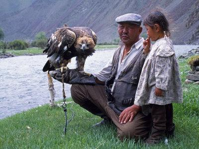 Mongolia, Kasakh Hunter with Eagle by the Khovd River, with a Small Child