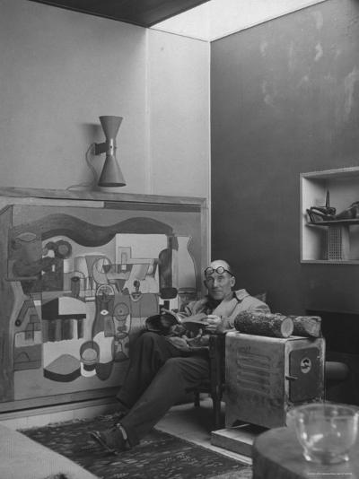 Architect Le Corbusier Sitting in Chair with Book in Hands, Glasses Perched on His Forehead-Nina Leen-Premium Photographic Print