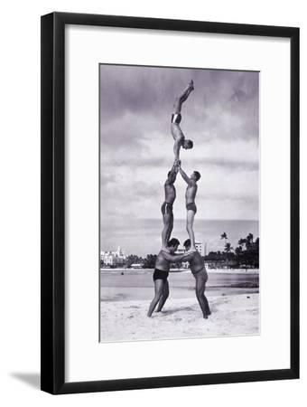 MEN AND GIRL PERFORM ACROBATICS ON BEACH