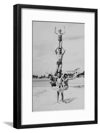 MEN AND GIRL PERFORM ACROBATICS ON BEACH