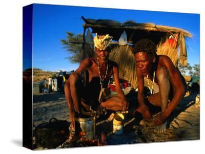 Kalahri Bushmen Cooking on Fire Outside Their Grass Homestead, South Africa