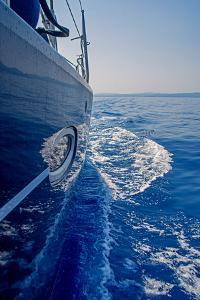 Luxury Navy Blue Sail Yacht is Sailing on High Speed in a Blue Sea with Waves Reflected in a Smooth by Artem Avetisyan