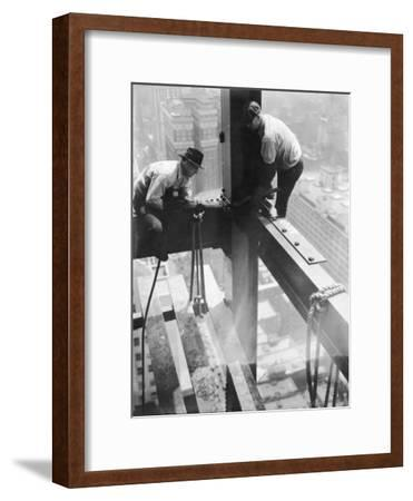 Workers balancing on steel beam above streets during construction of the Manhattan Company Building