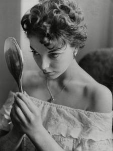 Joan Collins Studies Her Reflection by Associated Newspapers