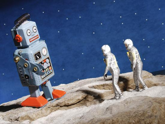 Astronaut Figurines Standing Beside Gray Toy Rocket--Photographic Print