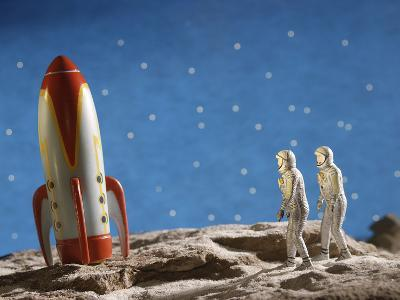 Astronaut Figurines Standing Beside Toy Rocket--Photographic Print