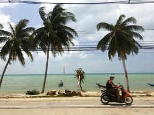 Motorcyclist Driving by Northern Coast of Ko Samui by Austin Bush