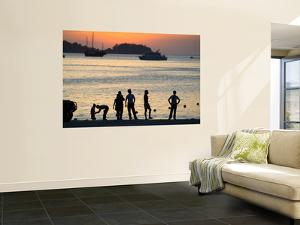 People on Patong Beach Silhouetted at Sunset by Austin Bush