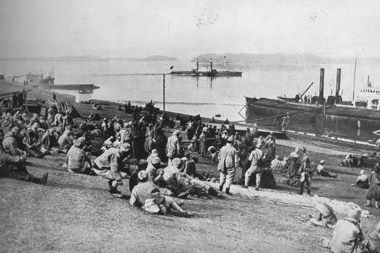 ''Austrian prisoners taken by Serbians resting at mid-day on the banks of the Danube', 1915-Unknown-Photographic Print