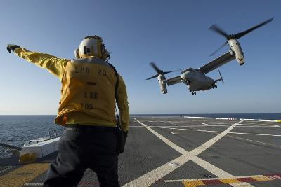 Aviation Boatswain's Mate Directs an MV-22 Osprey as it Launches from the Flight Deck--Photographic Print