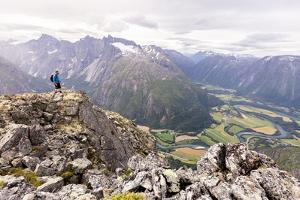 A Male Hiker On A Cliff Enjoying The View Over The Rauma (River) Valley In Norway by Axel Brunst