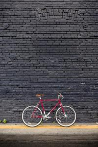 Beverly Hills, Los Angeles, California, USA: A Red Single Speed Bike In Front Of A Black Brick Wall by Axel Brunst