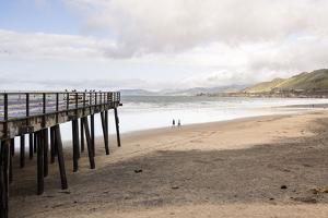 Pismo Beach Pier, California, USA: A Man And A Woman Walking Along The Beach by Axel Brunst