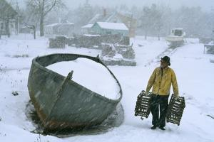 A lobsterman brings in two traps for repair during a blizzard by B.Anthony Stewart
