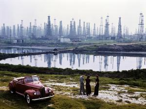 People chat by a car parked alongside a field of oil rigs, Signal Hill. by B^ Anthony Stewart