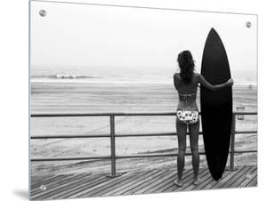 Model with Black Surfboard Standing on Boardwalk and Watching Wave on Beach by B.E.S.