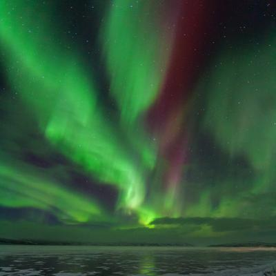 A Colorful Aurora Display over a Frozen Lake in Abisko National Park