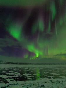 A Colorful Aurora Display over a Frozen Lake by Babak Tafreshi