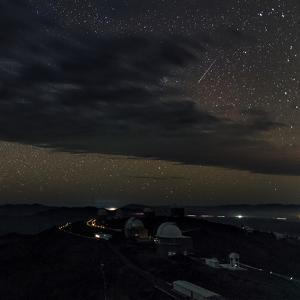 A Meteor Appears Next to the Beehive Star Cluster (M44) Above La Silla Telescope Domes by Babak Tafreshi