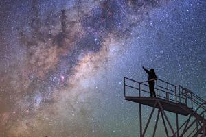 A Stargazer Points at the Constellations Scorpius and Sagittarius at the Cerro Paranal Observatory by Babak Tafreshi