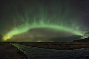 An Arc of Aurora Borealis Above a River in Southern Iceland by Babak Tafreshi