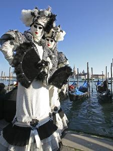 People wear elegant masks and costumes during Venice Carnival. by Babak Tafreshi
