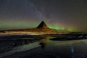 Starry sky and a faint band of aurora borealis above Kirkjufell mountain. by Babak Tafreshi