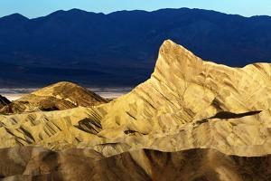 Sunlight on Eroded Landscape at Zabriskie Point. the Iconic Manly Beacon Formation Is Near Center by Babak Tafreshi