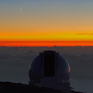 The New Moon Appears over the William Herschel Telescope by Babak Tafreshi