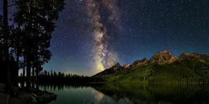 The Night Sky over a Lake in Grand Teton National Park by Babak Tafreshi