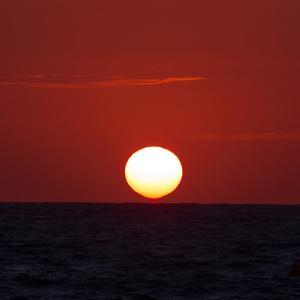 The Sun Sinks into the Atlantic Ocean, Off the Coast of Normandy, France by Babak Tafreshi