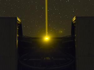 The Very Large Telescope at Night, Beaming a Laser to the Atmosphere for Adaptive Optics Operation by Babak Tafreshi
