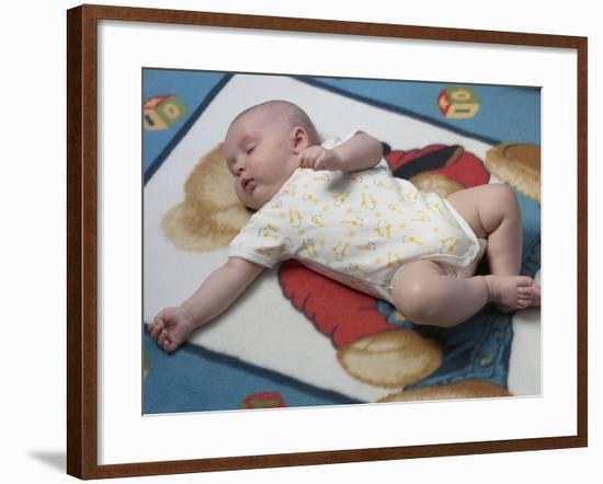 Baby in Yellow and White Sleeper Sleeping on Blanket--Framed Photographic Print