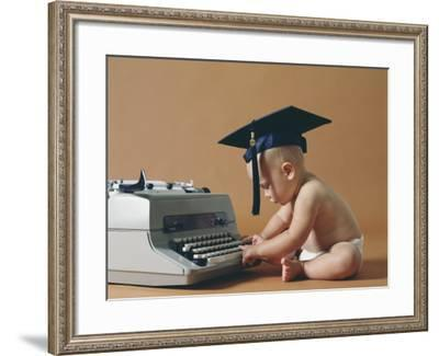 Baby Wearing Graduation Cap Typing on Typewriter-Dennis Hallinan-Framed Photographic Print