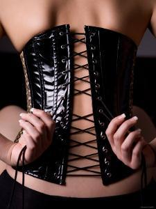 Back View of Woman Sitting and Tying Leather Corset