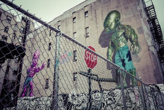 Backyard scene Graffiti of a pink and green superpower baby, Little Italy, Manhattan, New York, USA-Andrea Lang-Photographic Print