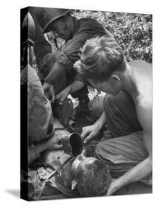 Badly Wounded Medic Being Given Water While Soldier in Background Cuts Clothing from His Wounds