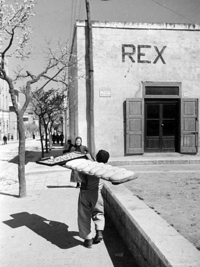 Baker's Apprentice Carrying a Large Tray of Bread Dough-Alfred Eisenstaedt-Photographic Print