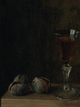 A Glass of Wine with Walnuts on a Table