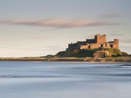 Bamburgh Castle Bathed in Golden Evening Light Overlooking Bamburgh Bay with the Sea Filling the Fo-Lee Frost-Photographic Print