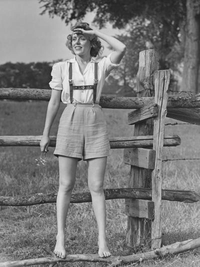 Barefoot Woman in Shorts Standing on Wooden Fence on Meadow-George Marks-Photographic Print