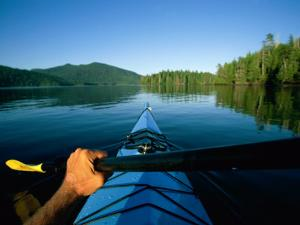 A Kayaker Sails Across This Serene Lake by Barry Tessman