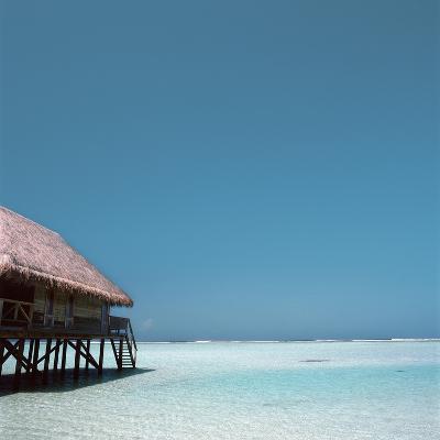 Beach Hut Over Shallow Water--Photographic Print