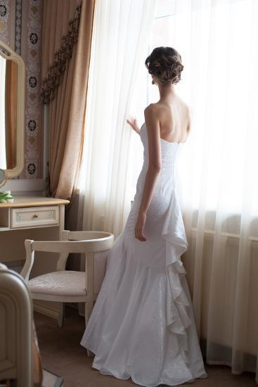 Beautiful Bride in White Wedding Dress Standing in Her Bedroom and Looking in Window- Malyugin-Photographic Print