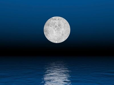 Beautiful Full Moon Against a Deep Blue Sky over the Ocean