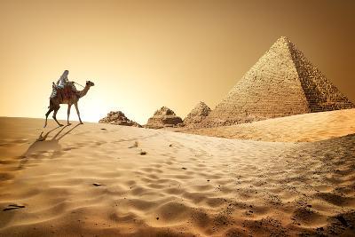 Bedouin on Camel near Pyramids in Desert- Givaga-Photographic Print