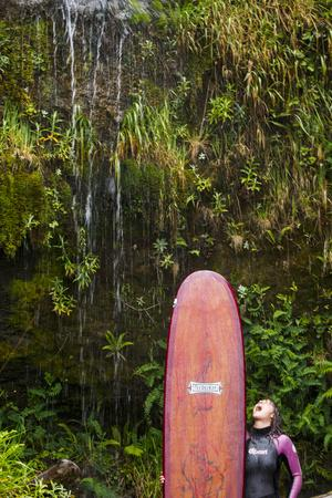 A Female Surfer Washes The Salt Off Her Board In A Lush Beach Waterfall Near Kalaloch Campground