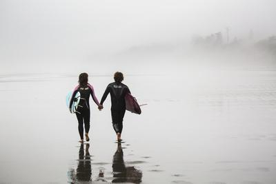A Male And Female Surfer Carry Their Surfboards While Holding Hand On Beach At Kalaloch Campground