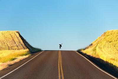 Alek Engerbretson Skateboarding Down A Rural Highway Near Oakesdale, Washington