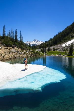 Female Backpacker Stands On A Floating Shelf Of Snow Melt On Small Lake Along E Lostine River Trail